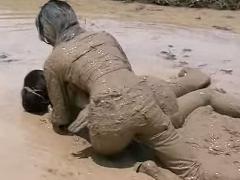 女性2人が泥の中に入り体を押さえつけあう